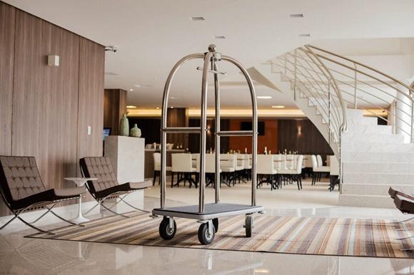 Lobby do hotel com poltronas marrons, carrinho de levar malas com gaiola prateada, ao fundo escada branca e restaurante com mesas e cadeiras brancas Blog Vem Por Aqui