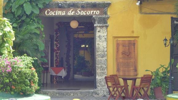 Entrada do restaurante com plantas do lado esquerdo e coluna de pedra do lado direito Blog Vem Por Aqui