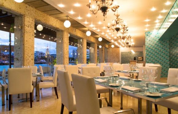 Salão do Marea, com parede da direita em papel azul estampado e da esquerda com vidro e granito. As mesas são de tampo de vidro e cadeiras de couro branco Blog Vem Por Aqui