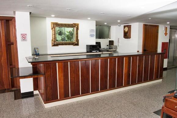 Recepção com balcão de madeira e espelho com moldura dourada Blog Vem Por Aqui