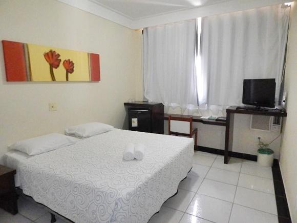 Quarto com cama coberta com colcha branca de matelassê, chão de cerâmica, quadro amarelo e vermelho acima, mesa de madeira, cadeira branca e frigobar Blog Vem Por Aqui