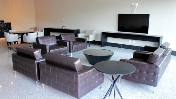 Recepção com sofás de couro marrom, TV, mesas pretas e, ao fundo, mesa de madeira com cadeiras brancas Blog Vem Por Aqui