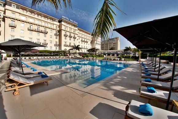 Piscina do hotel com espreguiçadeiras na frente e ao lado e prédio do hotel ao fundo com letreiro em cima escrito Hotel Palácio Blog Vem Por Aqui
