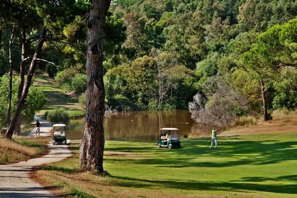 Campo de golfe com lago no fundo e estradinha para os carrinhos ao lado Blog Vem Por Aqui