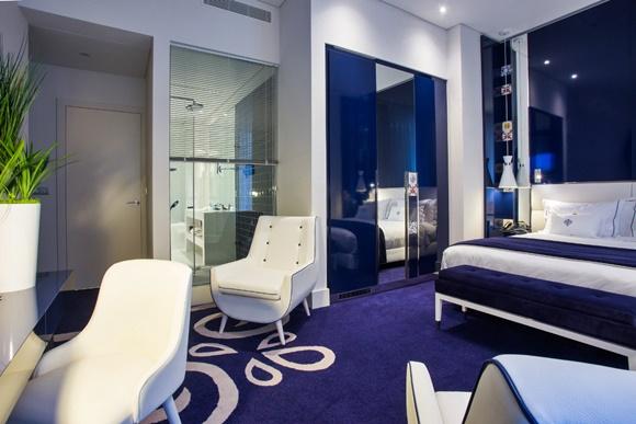 Quarto todo em azul e braco com cama de lençóis brancos e colcha azul e cadeiras de couro branco, ao fundo, no chão, tapete azul com desenhos em branco Blog Vem Por Aqui