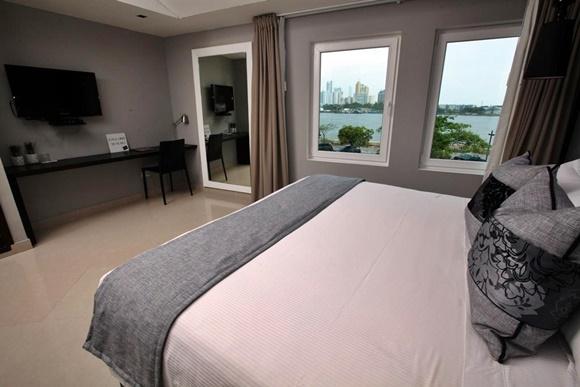 Quarto do Bon Bon com cama com almofadas em cinza e preto e janelas de vidro que dão pro mar Blog Vem Por Aqui