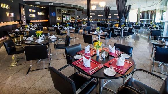 Mesa do restaurante com cadeiras pretas e mesas postas com jogos americanos vermelhos e louças brancas Blog Vem Por Aqui