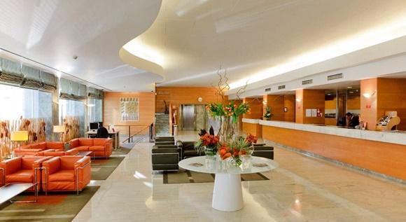 Lobby do hotel bem amplo com poltronas laranjas no canto e pretas no meio e recepção em frente Blog Vem Por Aqui