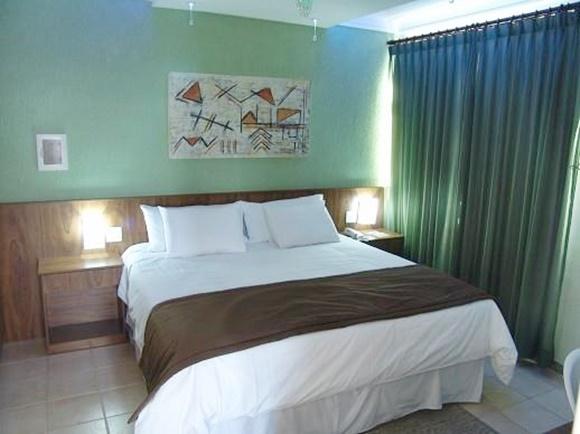 Quarto do hotel com cama coberta com edredom branco e colcha marrom atravessada. Parede verde e um quadro Blog Vem Por Aqui