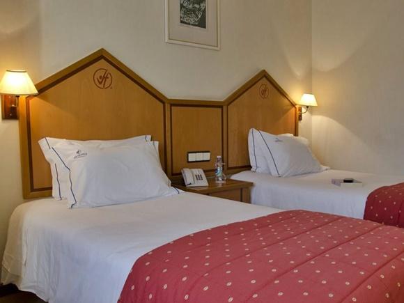 Quarto com camas em frente a painel de madeira com símbolo do hotel acima Blog Vem Por Aqui