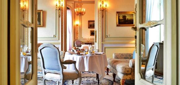 Salão de chá do Pestana com poltronas de estofado alto, antigas e mesa posta com café Blog Vem Por Aqui