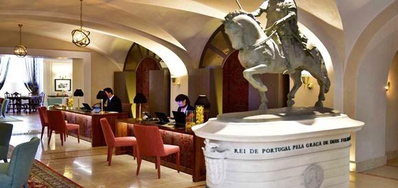 Recepção do hotel com estátua vista pela metada e mesas com recepcionistas Blog Vem Por Aqui