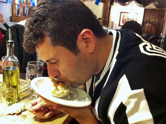 Homem com blusa do Atlético, de olhos fechado, beijando uma empanada no prato Blog Vem Por Aqui