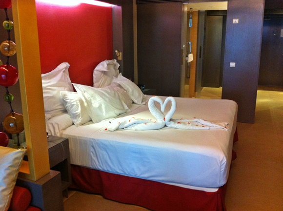 Cama com toalhas em formato de cisne e pétalas em cima do lençol Blog Vem Por Aqui