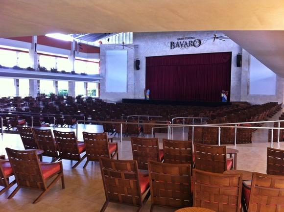 Teatro do hotel com cadeiras de madeira e palco com cortina vinho ao fundo Blog Vem Por Aqui
