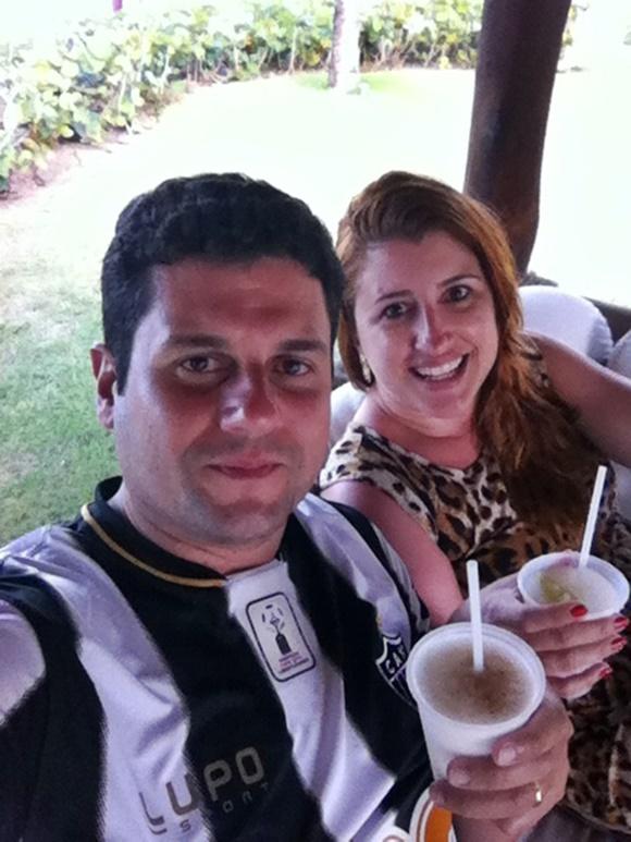 Mateus e Érika sorrindo e segurando copos com bebidas Blog Vem Por Aqui