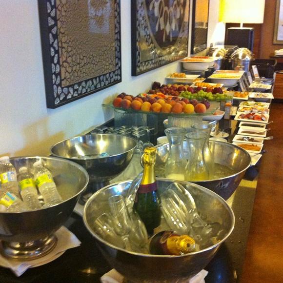 Mesa de café da manhã com bandejas de frutas e bowls com bebidas, garrafas de água e de espumante Blog Vem Por Aqui