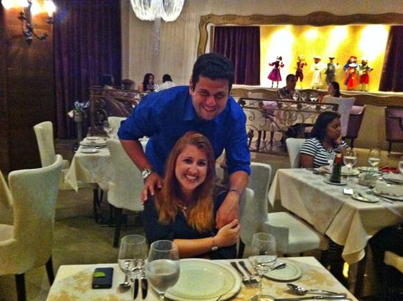 Érika sentada na cadeira e Mateus em pé, atrás, sorrindo, no meio do restaurante Blog Vem Por Aqui