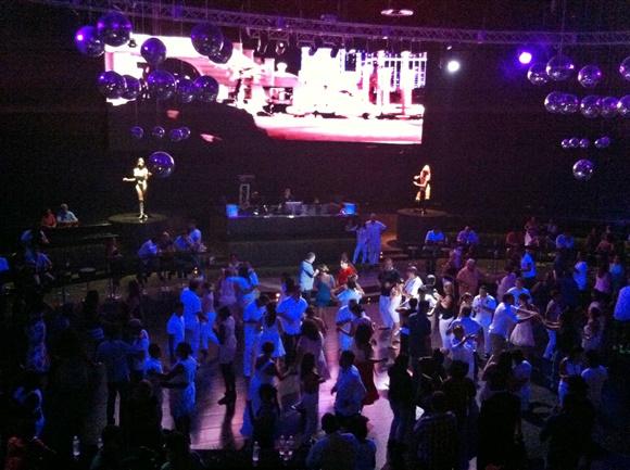 Pessoas na pista de dança na boate, diante do palco com duas dançarinas e um telão BLog Vem Por Aqui