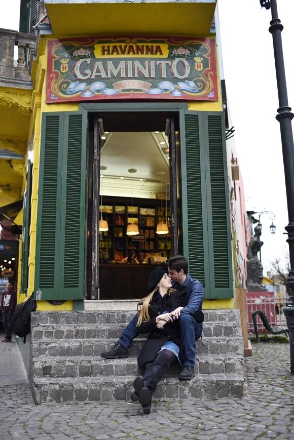 Casal sentado no degrau da loja de entrada da Havana no Caminito com portas verdes coloridas e letreiro com a marca Havana e, abaixo, pintada a palavra Caminito Blog Vem Por Aqui
