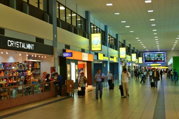 Lojas na lateral e pessoas no meio do corredor andando com malas Blog Vem Por Aqui