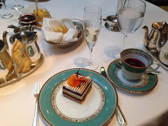 Mesa com pratos e copos de chá do hotel, dentro do prato um pedaço de bolo decorado e na xícara, o chá Blog Vem Por Aqui