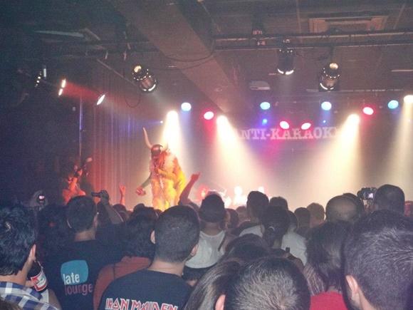 Homem com chapéu de viking estilizado com chifres grandes e boá amarelo no palco e nome da festa atrás, público à frente Blog Vem Por Aqui
