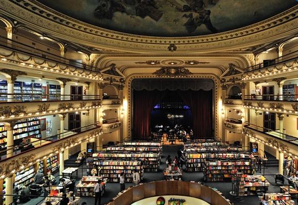 Parte interna da livraria vista de cima com estantes de livro em baixo, palco à frente e camarotes na lateral Blog Vem Por Aqui