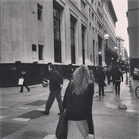 Mulher de costas, andando em rua com prédios antigos e luminárias com pessoas andando no mesmo calçadão Blog Vem Por Aqui