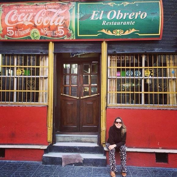 Mulher sentada na frente da fachada do restaurante que tem letreiro antigo da Coca-Cola e ao lado o do próprio restaurante Blog Vem Por Aqui