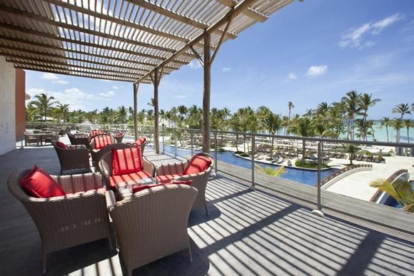 Deck do hotel com chão de madeira, sofás de palha com almofadas vermelhas, em frente à piscina