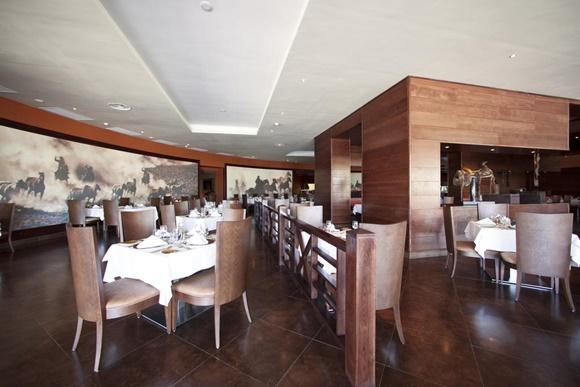 Restaurante com cadeiras de madeira e couro e mesas com toalhas brancas Blog Vem Por Aqui
