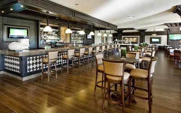 Bar do hotel com mesas e cadeiras altas e balcão com várias cadeiras Blog Vem Por Aqui