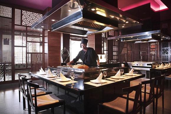 Cozinheiro no meio da estação do restaurante japonês com cadeiras em volta Blog Vem Por Aqui
