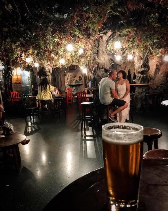 Copo de cerveja à frente das mesas do bar com alguns clientes e folhagem no teto Blog Vem Por Aqui