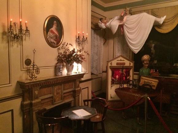 Sala do bar com quadro antigo em cima de dama antiga em cima de uma lareira, com mesa na frente, ventríloquo ao lado e manequim vestido de branco como se levitasse no teto Blog Vem Por Aqui