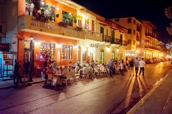 Bar em casa antiga do centro histórico com mesas na rua e pessoas passeando a pé Blog Vem Por Aqui