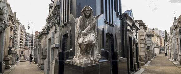 Cemitério com tumbas dos dois lados e, ao centro, uma com mármore preto e anjo sentado na frente Blog Vem Por Aqui