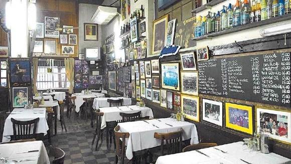 Parte interna do restaurante com paredes cheias de quadros com fotos Blog Vem Por Aqui