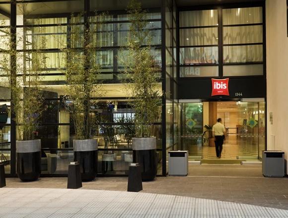 Fachada do hotel toda de vidro com três árvores compridas, tipo bambu Blog Vem Por Aqui
