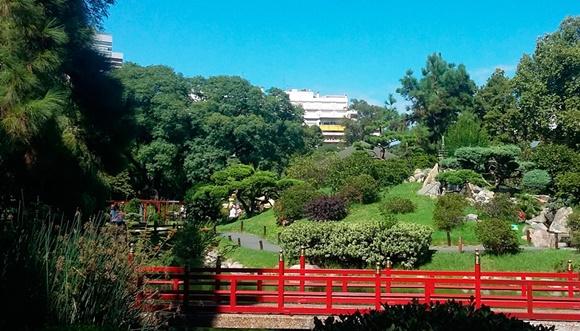 Ponte vermelha com várias árvores e plantas abaixo Blog Vem Por Aqui