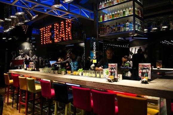 Bar do Johnny com cadeiras altas coloridas, balcão de madeira, atendentes do lado interno e letreiro com as palavras The Bar iluminadas
