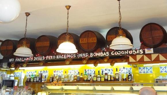 Balcão do bar com lustres brancos e barris em cima de uma inscrição que diz: No Hablamos Ingles Pero Hacemos Unas Bombas Cojonudas Blog Vem Por Aqui