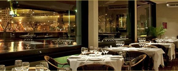 Salão interno do Marcelo com mesas com várias taças e janela de vidro que dá pro rio Blog Vem Por Aqui