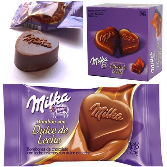 Mosaico com três fotos, na primeira o bombom em forma de coração escrito Milka em chocolate em com a embalagem desfocada no fundo, ao lado a caixa do bombom e abaixo a embalagem individual Blog Vem Por Aqui