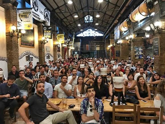 Galpão grande do bar com mesas grandes lotadas de clientes Blog Vem Por Aqui