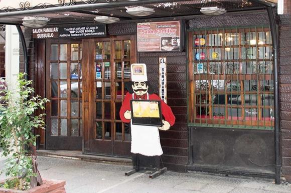 Fachada do Sanjuanino com placa tipo estátua de mestre-cuca na frente segurando o cardápio Blog Vem Por Aqui