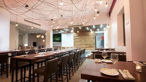 Restaurante do Tântalo com mesa grande de madeira e mesas menores ao lado, no teto, várias luminárias com fios entrelaçados Blog Vem Por Aqui