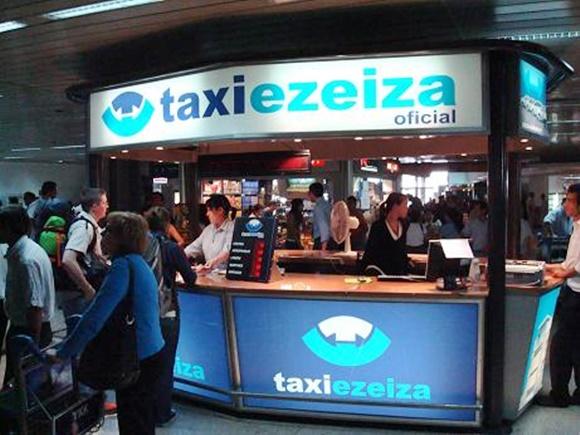 Guichê de atendimento da Táxi Ezeiza com atendentes do lado de dentro e letreiros grandes em cima e abaixo com o nome da empresa. Em frente a ele, pessoas no aeroporto Blog Vem Por Aqui