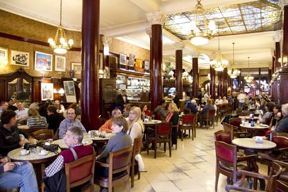 Clientes nas mesas do Café Tortoni e teto com vitrô e lustres antigos Blog Vem Por Aqui